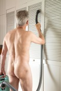 Nude Mature Man Vacuuming Folding Doors in Home, USA. Image shot 2013. Exact date unknown.